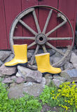Yellow rubber boots near carriage wheel Royalty Free Stock Images