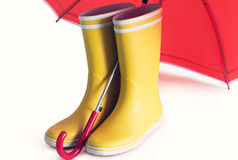 Yellow rubber boots and open red umbrella Stock Photo