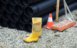 Yellow rubber boots and plastic tubes in road construction Stock Photos
