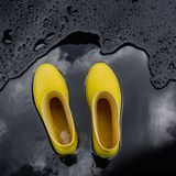 Yellow rubber boots stand in a puddle in which the clouds are reflected. Black background, top view stock photography