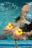 Yellow rubber duck in hands at swimming pool. Stock Image