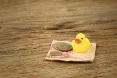 Yellow rubber duck with Thai Bath money. Stock Photo