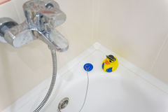 Yellow rubber duckie on edge of bathtub Stock Photo