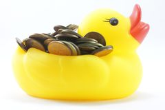 Yellow rubber ducks. Are carrying a large silver coin on the back Stock Image