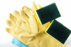 Yellow rubber glove and scrubber sponges on blue cleaning napkin Royalty Free Stock Images