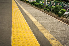 Yellow rubber sign with arise dots to direct blind people at Depok station photo taken in Depok Indonesia. Java stock images