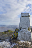 Yellow rucksack next to a trig point on the top of a mountain in Scotland, snow on the ground Stock Photo