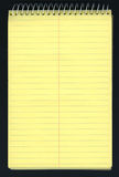 Yellow ruled spiral notepad over black Royalty Free Stock Photography