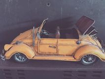 Yellow rustic car model. Sitting on ledge stock image