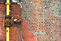 Yellow rusty gas pipe with valve on red brick wall, grunge texture. Background stock image