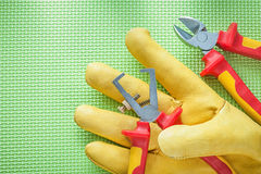 Yellow safety gloves insulation strippers nippers on green backg Royalty Free Stock Photo