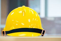 Yellow safety hard hat with blur background. Yellow safety hard hat with black bar lay on table with blurry background Royalty Free Stock Photos