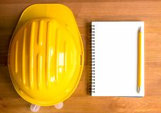 Yellow safety hard hat with notebook and pencil on a wooden background royalty free stock image
