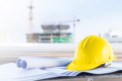 The yellow safety helmet and the blueprint at construction site. With crane background royalty free stock images