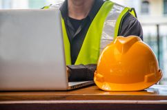 The yellow safety helmet and Business man in Construction industry is working in on computer. On the background royalty free stock images