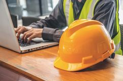 The yellow safety helmet and Business man in Construction industry is working in on computer. The yellow safety helmet and Business man in Construction industry stock images