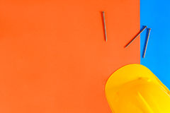 Yellow safety helmet and Construction materials on paper blue an Royalty Free Stock Photo