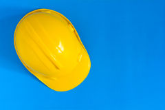 Yellow safety helmet and Construction materials on paper blue an Royalty Free Stock Image