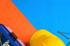 Yellow safety helmet and Construction materials on paper blue an Stock Image