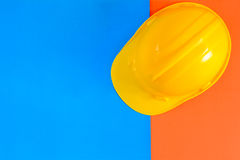 Yellow safety helmet and Construction materials on paper blue an Stock Photos