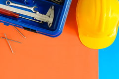 Yellow safety helmet and Construction materials on paper blue an Royalty Free Stock Photography