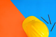 Yellow safety helmet and Construction materials on paper blue an Royalty Free Stock Photos