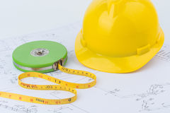 Yellow safety helmet and Green measuring tape Stock Photos