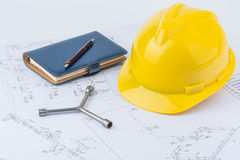 Yellow safety helmet, Spanner and notebook Royalty Free Stock Images