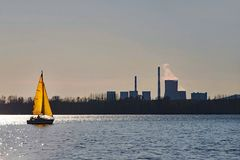 Yellow sailboat on the lake, in the background the electorate with smoking chimneys royalty free stock photos