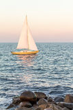 Yellow sailboat in the ocean with stones in foreground Royalty Free Stock Photos