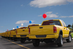 Yellow Sale. A long row of nothing but yellow pickups is lined up along the street with ballons attached to get the attention of passersby Stock Images