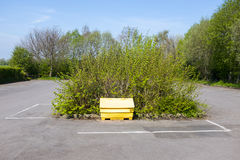 Yellow salt and grit bin UK. Yellow salt and grit container on empty parking lot UK Royalty Free Stock Photography