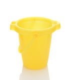 Yellow Sand Bucket on White. Closeup of a yellow sand bucket over a white background with reflection royalty free stock photos