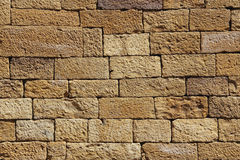 Yellow sand stone wall for background or texture. Closeup of gold sand brick wall Stock Image