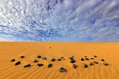 Yellow sand. Summer dry landscape in Africa. Black pebble stone. Royalty Free Stock Image