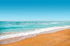 Yellow sand and turquoise color waters at swimming area of sea with lots of people learning how to surf - Jeju Island, South Korea. Yellow sand and turquoise Royalty Free Stock Photography