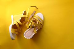 Yellow sandals on a yellow background and a place for an inscription. Yellow, background, isolated, female, style, sandal, fashion, summer, walking, footwear royalty free stock photos