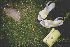 Yellow sandals and a handbag on the green grass Stock Photos