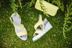 Yellow sandals and a handbag on the green grass Royalty Free Stock Photos