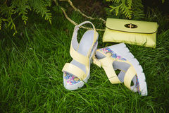 Yellow sandals and a handbag on the green grass Royalty Free Stock Photography
