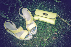 Yellow sandals and a handbag on the green grass Royalty Free Stock Photo