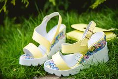 Yellow sandals and a handbag on the green grass Stock Image