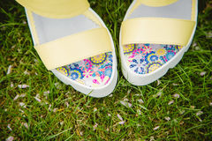 Yellow sandals and a handbag on the green grass Stock Photo