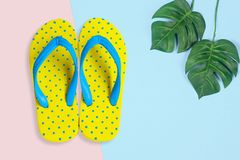 Yellow sandals with shell on blue color background. Summer holidays accessories . flat lay photo stock images
