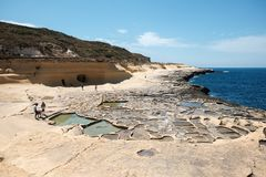Malta and Gozo islands. Yellow sandstone rocks and caves and salt pans at the sea, near to Marsalforn, Gozo island, Malta Stock Photo