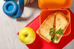 Yellow sandwich box with toasted slices of bread, cheese and green parsley, green apple, headphones and hardback books on. The background. School breakfast stock photos