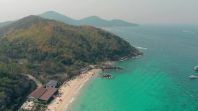 Yellow sandy beach near turquoise ocean water upper view. Wonderful yellow sandy beach washed by turquoise ocean water with forestry hills on horizon upper view stock footage