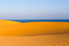 Yellow sandy wavy dunes with blue sea at background Stock Photography