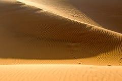 Yellow sandy wavy dunes in desert at daytime Royalty Free Stock Photos
