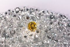 Yellow sapphire diamonds are placed on a pile of white diamonds